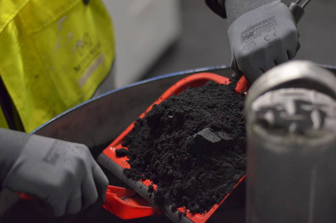 Operator adding iron powder to wastewater treatment process