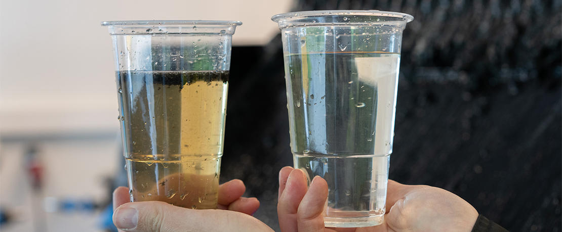 Hands holding cups with treated leachate